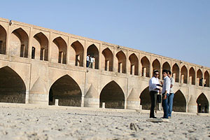 Iranians standing in dried river bed of Zayandehrud river in Isfahan