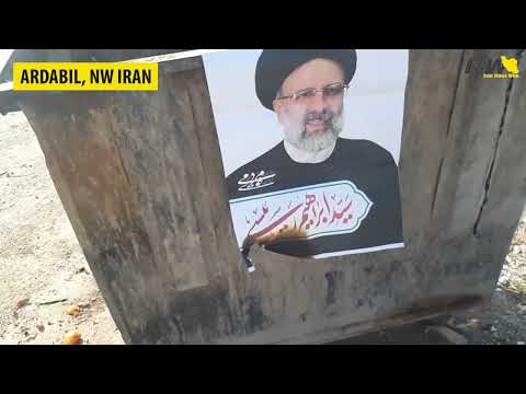 Iranians tearing down and burning election posters