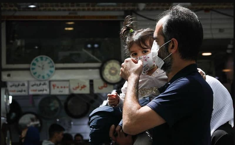 Iranian man fixing his daughter's mask against Covid-19