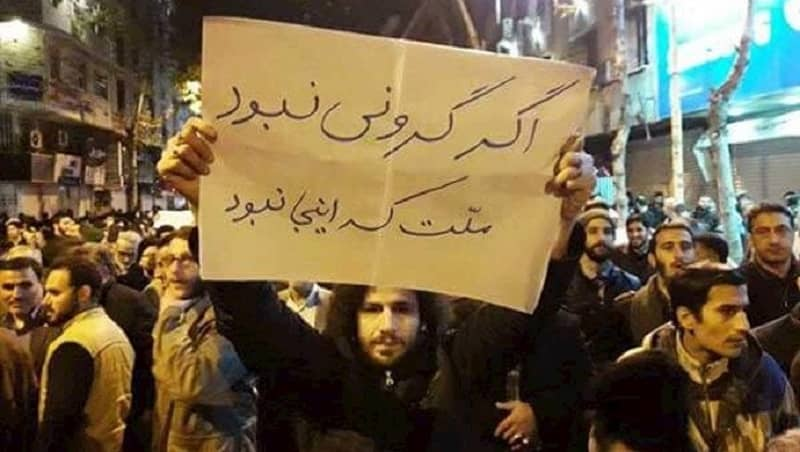 protes-iran-pria-memegang-papan