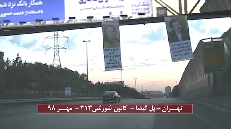 Banners of the Iranian opposition leaders (Massoud Rajavi and Maryam Rajavi) hung from a pass-over in one of Tehran's main motorways